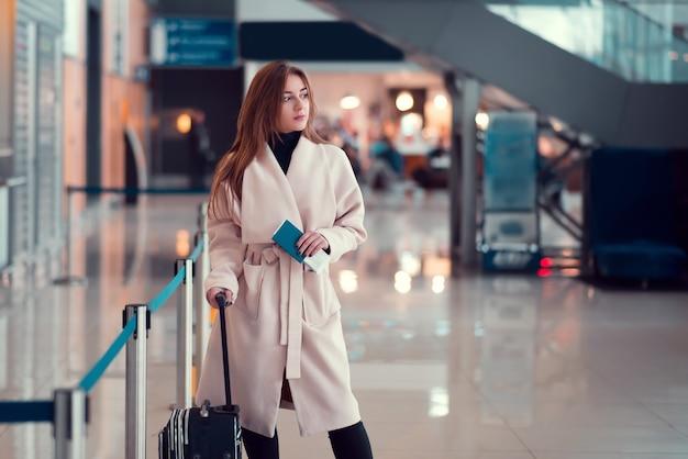 Chica joven con una maleta en el aeropuerto.