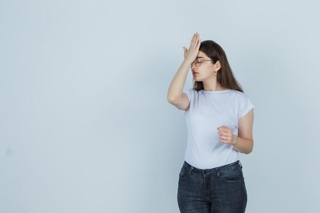 Chica joven con la mano en la frente en camiseta, jeans y aspecto cansado. vista frontal.