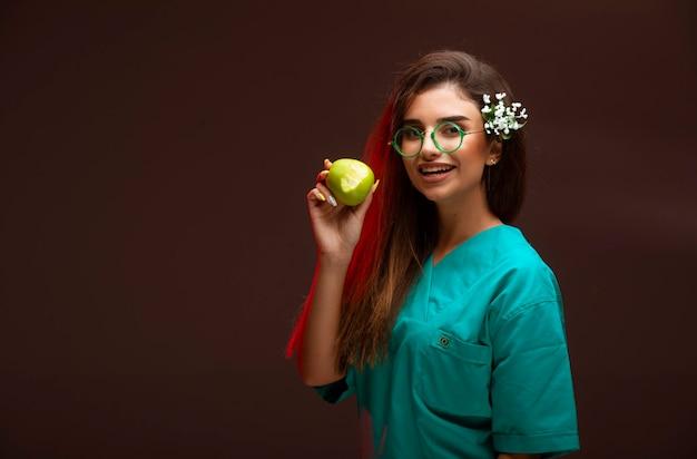 Chica joven con una manzana verde en la mano.