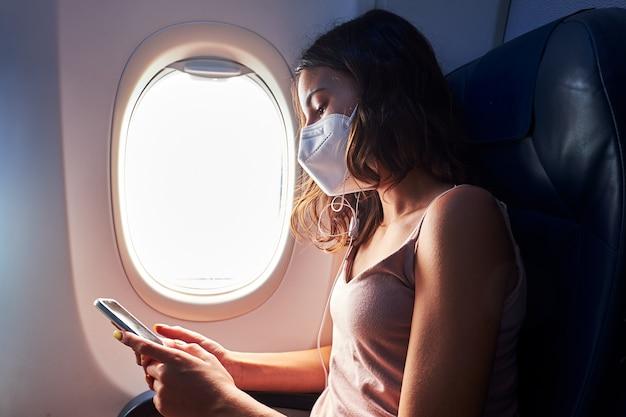 Chica joven con máscara facial con smartphone mientras viaja en avión