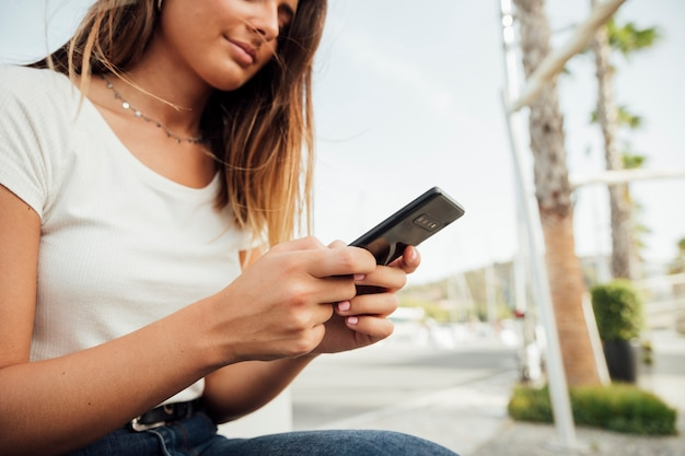 Chica joven con mensajes de texto de teléfono inteligente