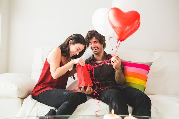 Chica joven mirando una bolsa roja mientras su novio sujeta globos rojos y blancos