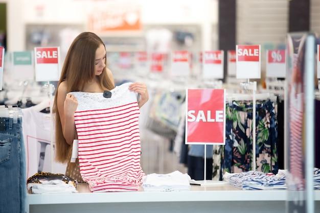 Chica joven mirando una falda de rayas rojas y blancas