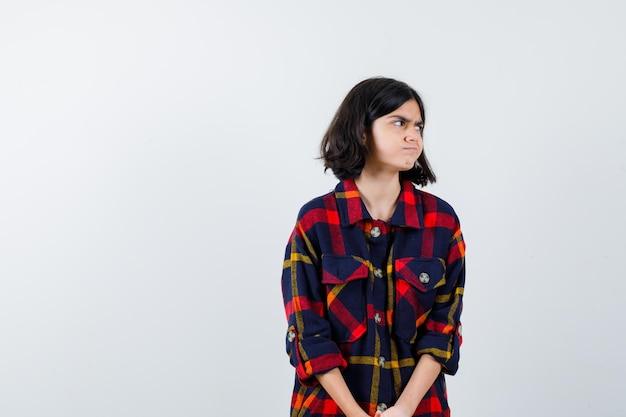 Chica joven mirando a otro lado mientras posa con camisa a cuadros y mirando serio, vista frontal.