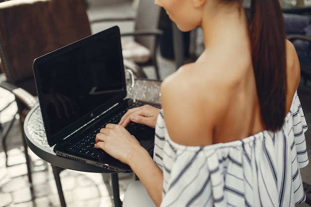 Chica joven de la moda que se sienta en un café del verano