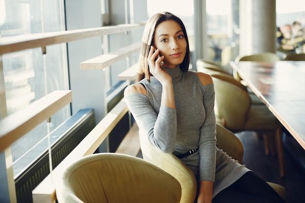 Chica joven de la moda que se sienta en un café
