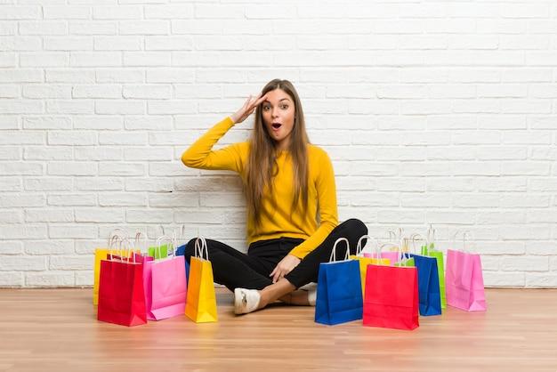 Una chica joven con muchas bolsas de compras acaba de darse cuenta de algo y tiene la intención de encontrar la solución