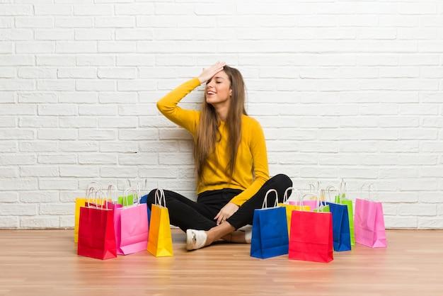 Una chica joven con muchas bolsas de compras acaba de darse cuenta de algo y tiene la intención de resolver