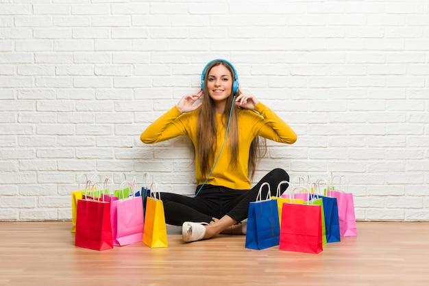 Chica joven con muchas bolsas de compras escuchando música con auriculares