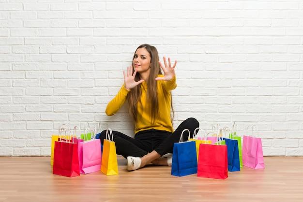 La chica joven con muchas bolsas de compras está un poco nerviosa y asustada estirando las manos al frente