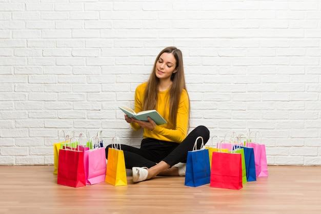 Chica joven con muchas bolsas de compras sosteniendo un libro y disfrutando de la lectura