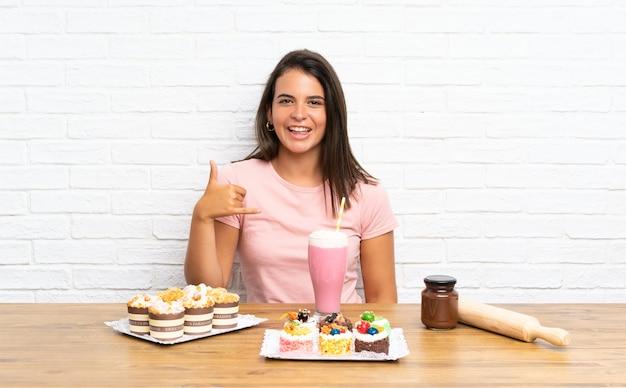 Chica joven con muchas mini tortas diferentes haciendo gesto de teléfono