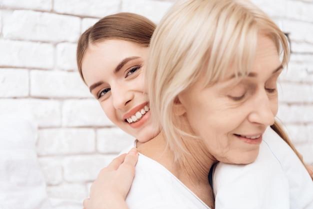 Chica joven y mujer mayor que abrazan en clínica junto.