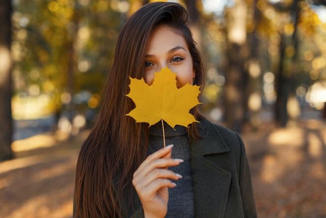 Chica joven muy elegante con ojos azules en un abrigo de moda, sosteniendo una hoja de otoño amarilla cerca de la cara mientras camina en el parque. mujer sonriente.