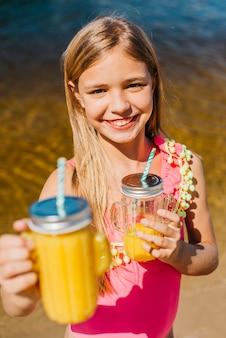 Chica joven ofrece bebidas mientras está de pie en la playa