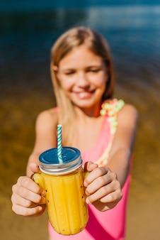 La chica joven ofrece el tarro con el jugo mientras que se coloca en la playa
