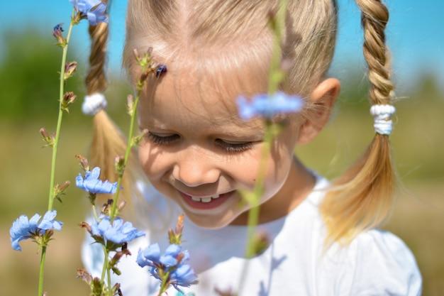 Chica joven oliendo flores silvestres azules jugando un día de verano