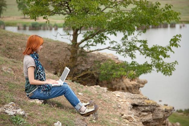 Chica joven con el ordenador portátil que se sienta en una batería del lago.