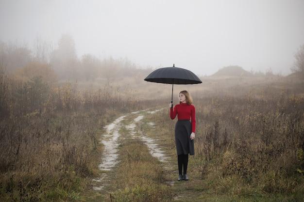 Chica joven con paraguas en campo de otoño