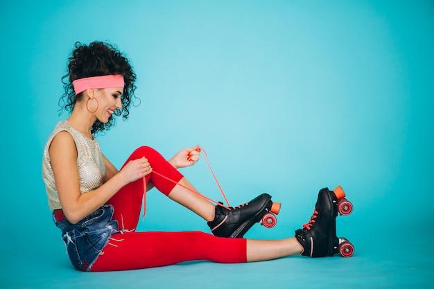 Chica joven con los patines de ruedas aislados