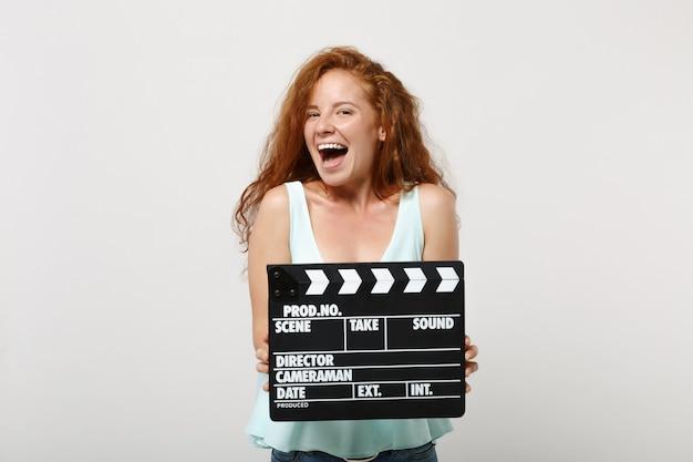 Chica joven pelirroja alegre en ropa casual ligera posando aislada sobre fondo blanco en estudio. concepto de estilo de vida de personas. simulacros de espacio de copia. sosteniendo claqueta de cine negro clásico.