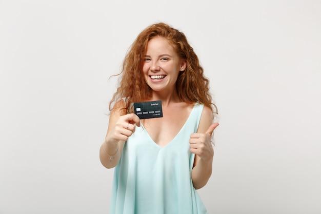 Chica joven pelirroja alegre en ropa casual ligera posando aislada sobre fondo blanco, retrato de estudio. concepto de estilo de vida de personas. simulacros de espacio de copia. sosteniendo la tarjeta bancaria de crédito mostrando el pulgar hacia arriba.