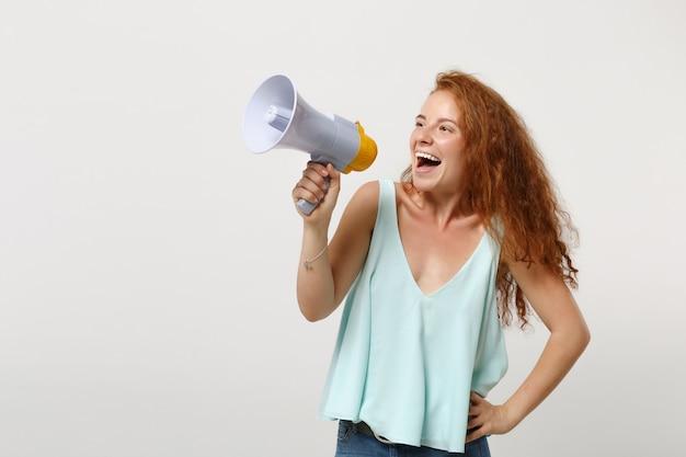 Chica joven pelirroja alegre en ropa ligera casual posando aislada sobre fondo de pared blanca, retrato de estudio. concepto de estilo de vida de emociones sinceras de personas. simulacros de espacio de copia. grita en megáfono.