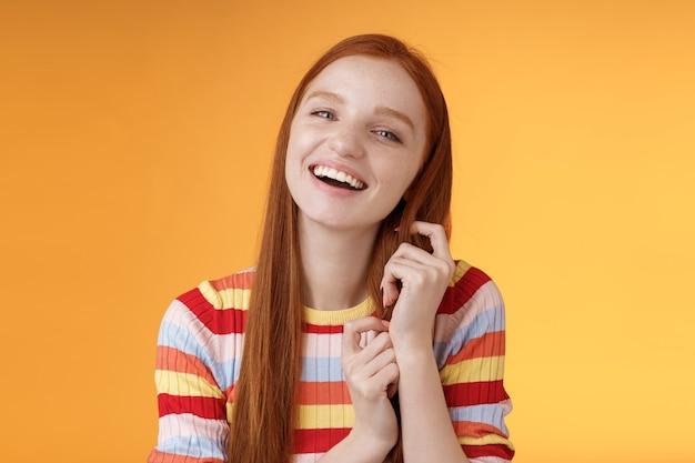 Chica joven pelirroja animada coqueta atractiva y tonta riendo jugando coqueto mechón de pelo de jengibre riendo entre dientes divertidos chistes divertidos de novios divirtiéndose increíble cita romántica, fondo naranja.