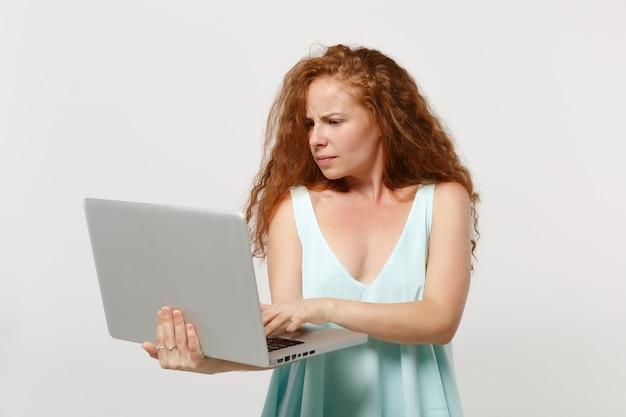 Chica joven pelirroja desconcertada en ropa ligera casual posando aislado en retrato de estudio de fondo de pared blanca. concepto de estilo de vida de personas. simulacros de espacio de copia. sosteniendo el trabajo en la computadora portátil.