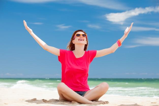 Chica joven pelirroja feliz en gafas de sol con las manos en la costa del mar de verano.