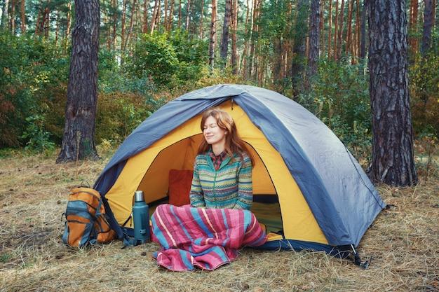 Chica joven pelirroja con los ojos cerrados, sentado en la tienda gris amarillo, relajante, disfrutando de la naturaleza en el bosque de otoño