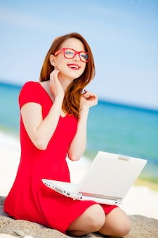 Chica joven pelirroja en vestido rojo y computadora descansar en la playa del mar de verano