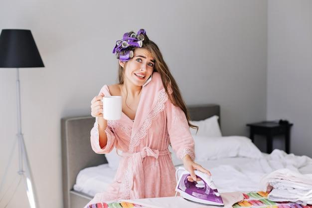 Chica joven con pelo largo en bata de baño rosa y rizador en la cabeza sosteniendo una plancha y hablando por teléfono en casa. ella parece asombrada.