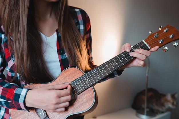 La chica joven con el pelo largo en una camisa roja juega en ukuded sentado en casa.