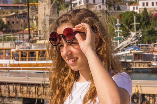 Chica joven con el pelo largo en el muelle en el puerto de yates