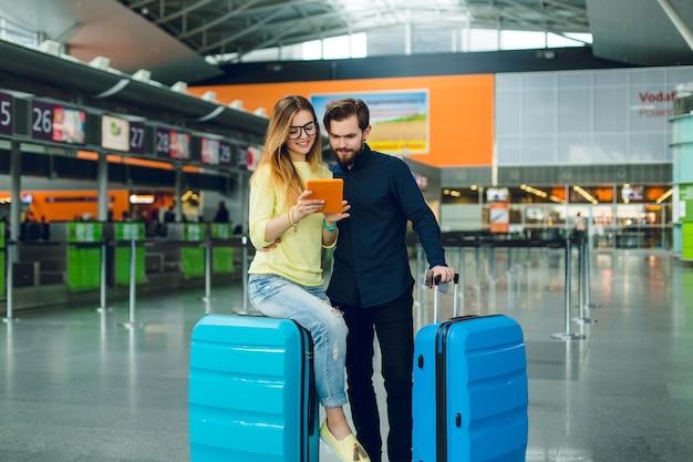 Chica joven con pelo largo en suéter amarillo, jeans está sentada en la maleta en el aeropuerto. chico con barba en camisa negra con pantalones y maleta está parado cerca. están buscando en tableta.