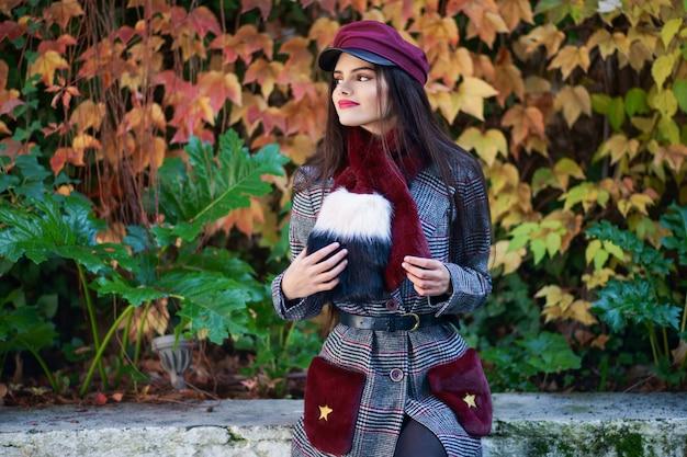 Chica joven con el pelo muy largo sonriendo y vistiendo abrigo de invierno y gorra en otoño sale del fondo