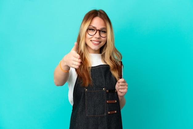 Chica joven peluquero sobre fondo azul aislado un apretón de manos para cerrar un buen trato