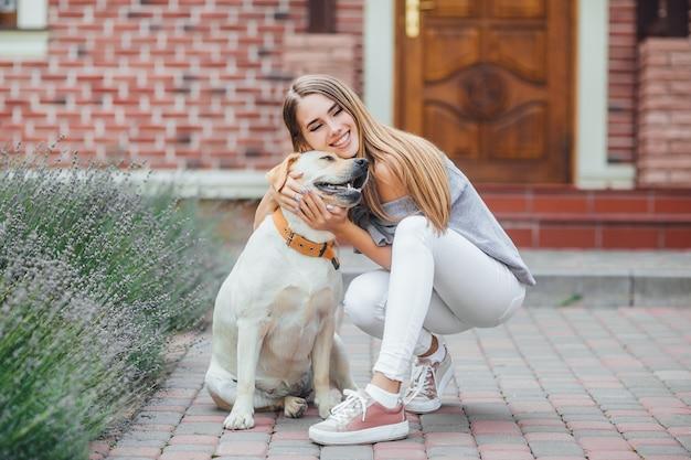 Chica joven con perro perdiguero en caminata en frente de la casa. mujer atractiva abrazando a su labrador retriever.