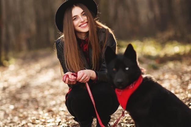 Chica joven con un perro que camina en el parque del otoño