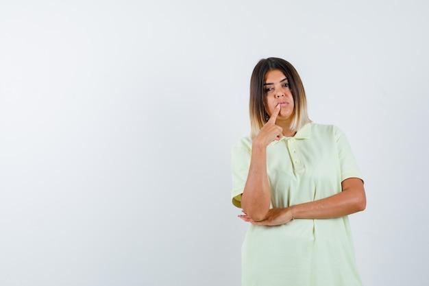 Chica joven poniendo el dedo índice cerca de la boca, sosteniendo la mano debajo del codo mientras posa en una camiseta y luce atractiva. vista frontal.