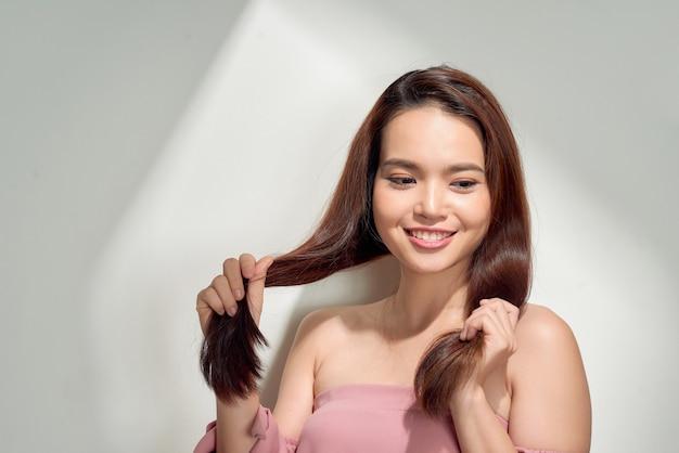 Chica joven posando junto a la pared blanca sonriendo. mujer de verano. primavera cálida