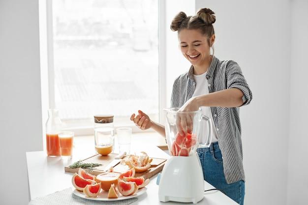 Chica joven positiva que corta el pomelo que mezcla el smoothie fresco de la desintoxicación sana sobre la pared blanca.