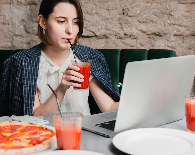 Chica joven que bebe batido y trabajando en la computadora portátil