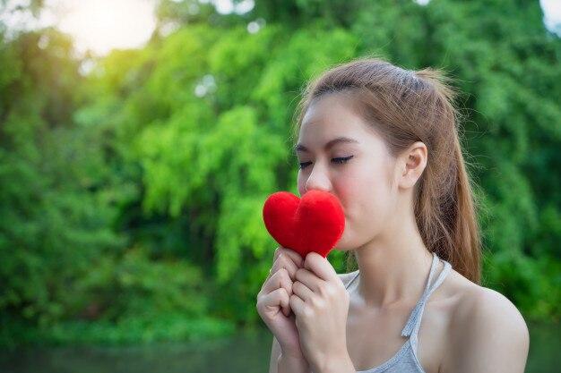 Chica joven que besa el corazón rojo. mujer modelo con corazón rojo. beso femenino símbolo de amor.