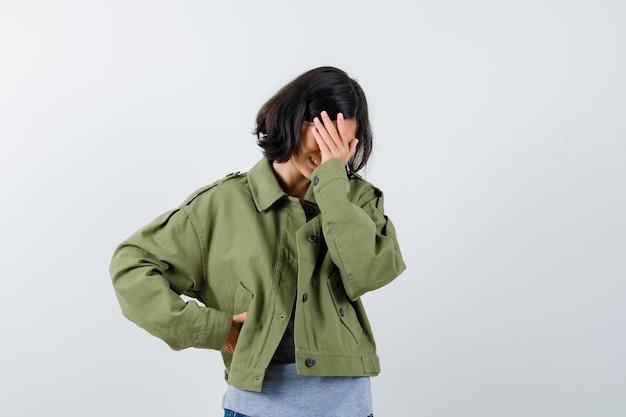Chica joven que cubre la cara con la mano sosteniendo la mano en la cintura en suéter gris, chaqueta de color caqui, pantalón de mezclilla y mirando acosado. vista frontal.
