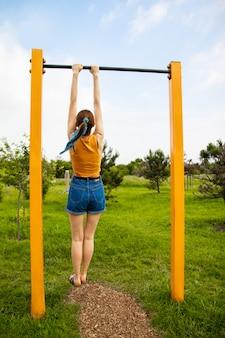 Chica joven que cuelga en una barra horizontal.