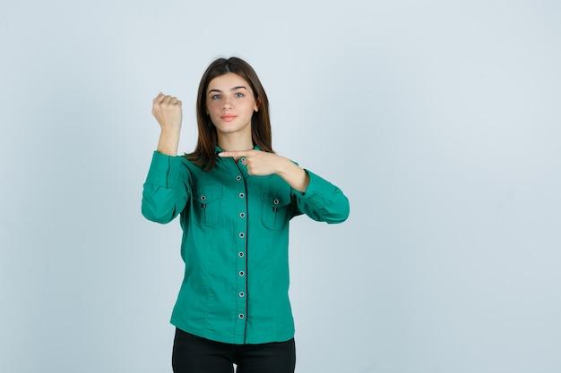Chica joven que finge señalar el reloj en su muñeca en blusa verde, pantalón negro y mirando feliz, vista frontal.