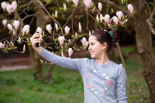 Chica joven que hace el selfie en el parque de la primavera