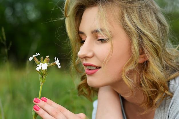 Chica joven que huele la flor salvaje salvaje en el campo